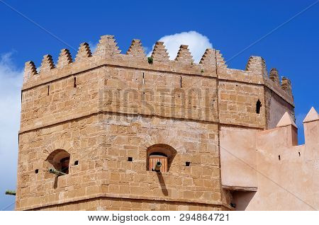 Terraced Pinnacles On Top Of Fortified Tower With Gun Barrels In Crenels At City Wall Of Casbah Of T