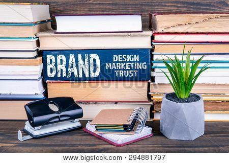 Brand Concept. Design, Marketing And Trust. Books Stacked On A Wooden Table