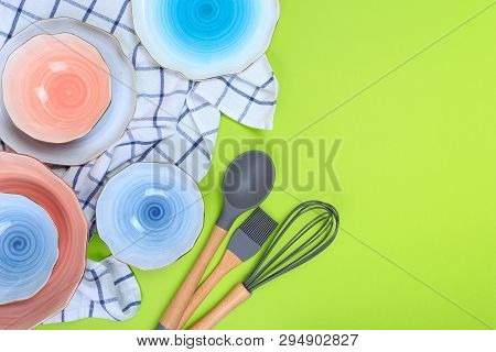 Various Kitchen Utensils, Plates And A Towel On A Green Background. Top View. Kitchen Appliances.