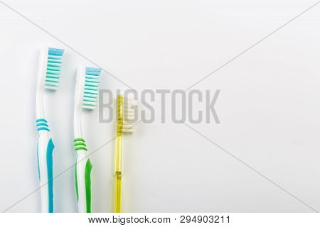 New Different Colored Toothbrushes On A White Background