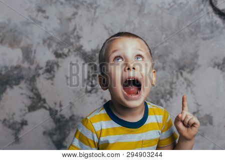 A Little Boy Poses In Front Of A Gray Concrete Wall. Portrait Of A Screaming Child With Open Mouth,