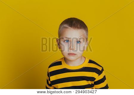 Portrait Of Attractive Serious Boy With In A Striped Sweater Close-up, On A Yellow Background