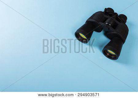 Black Binoculars With Orange Lens On Blue Background