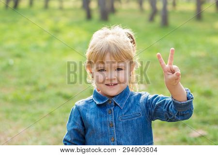 Portrait Of Happy Little Girl With Smile On Face On Sunny Day In Park