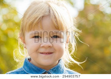 Little Happy Girl In A Denim Jacket Smiling And Looking At The Camera