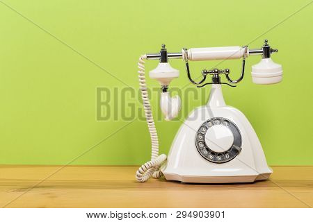 Vintage Old White Telephone On Wooden Table With Color Wall Background
