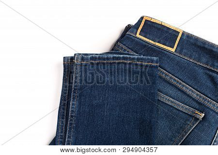 Stack Of Various Shades Of Blue Jeans On White Background