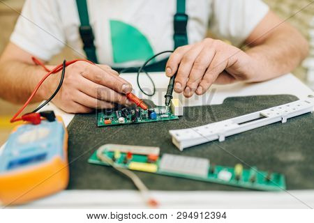 Electrician in uniform checks the chip, handyman