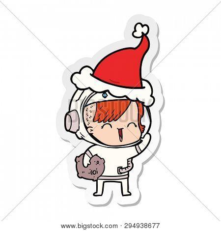 hand drawn sticker cartoon of a happy spacegirl holding moon rock wearing santa hat