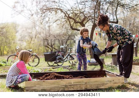Mother with two young daughters gardening in urban community garden