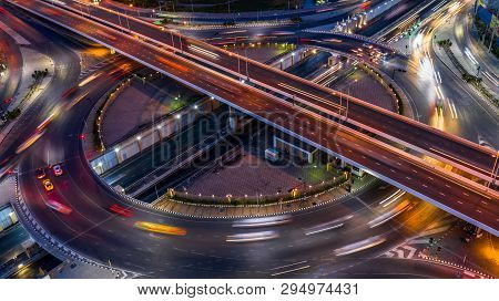 Road Roundabout Intersection In The City At Night With Vehicle Car Light Movement, Aerial View.
