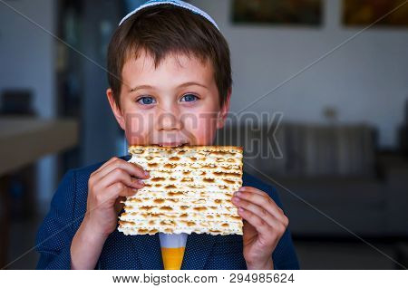 Cute Caucasian Jewish Boy Holding In His Hands And Taking A Bite From A Traditional Jewish Matzo Unl
