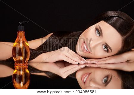 Beautiful Girl On Black Glass With Hair Oil