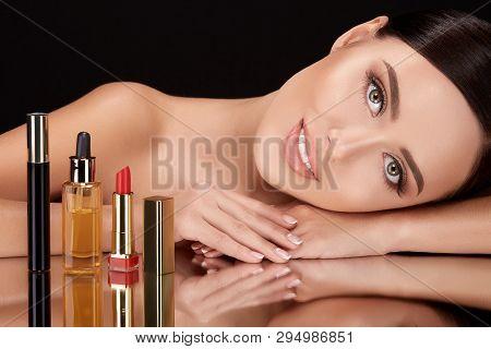 Beautiful Woman On Black Glass With Cosmetics