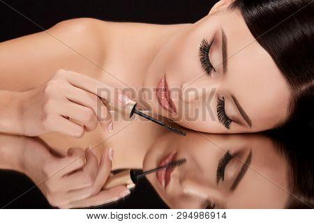 Beautiful Woman On Black Glass With Mascara