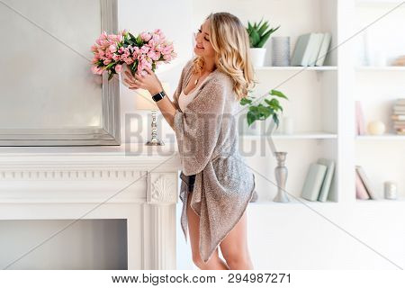 Young Blonde Woman Decorating Room With Beautiful Flowers. Beautiful Woman Arranging Flowers And Dec