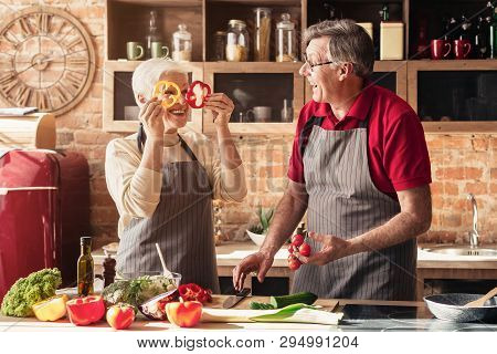 Senior Couple Having Fun On Kitchen. Playful Woman Making Faces With Pepper Slices, Free Space