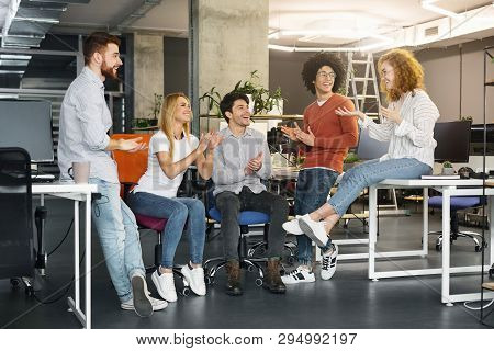 Welcome To Team. Cheerful Coworkers Welcoming New Colleague In Modern Coworking Space