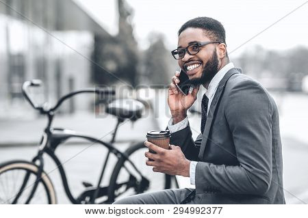No Time For Break. Millennial Businessman Talking On Phone During His Lunch Outdoors With Bicycle Ne