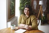 Pretty girl with chubby cheeks and curvy body doing home assignment sitting coworking space with blank empty diary and mug. Stylish plus size woman drinking cappuccino, making notes in copybook poster
