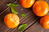 Group of four whole fresh orange mandarine with green leaves one fruit is half peeled flatlay on brown wood poster