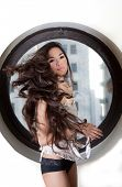 Pretty Sexy Hispanic Woman wth Beautiful Long Hair sitting in the a circle window with city buildings in the background poster