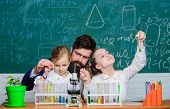 How to interest children study. Fascinating biology lesson. Man bearded teacher work with microscope and test tubes in biology classroom. School biology experiment. Explaining biology to children poster