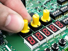 Closeup Of A Technician's Hands Checking Electronic Pcb (printed Circuit Board) With Microchips Proc