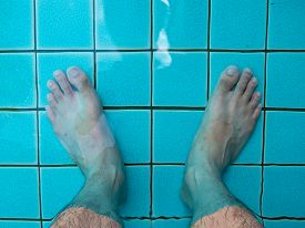 Legs In The Pool Water. Summer Traveling Background.
