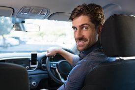 Portrait of handsome man driving car to work. Smiling casual businessman turning behind while sitting on driver seat. Satisfied young man driving his new car while looking at camera.