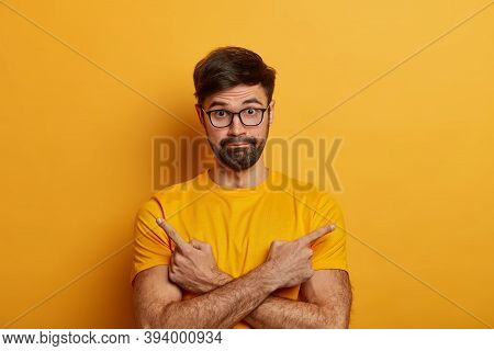 Perplexed Unsure European Man Crosses Hands And Points Sideways, Chooses Between Two Objects, Should
