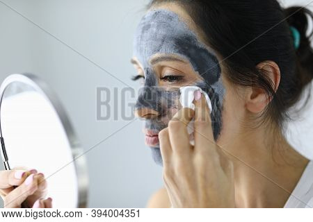 Woman Looks In Mirror And Rinses Off An Anti-aging Face Mask With Cotton Pad. Facial Treatments At H
