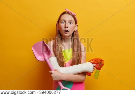 Children, Leisure And Games Concept. Shocked Little Girl Plays Water Gun, Holds Sand Shovel, Has Fun