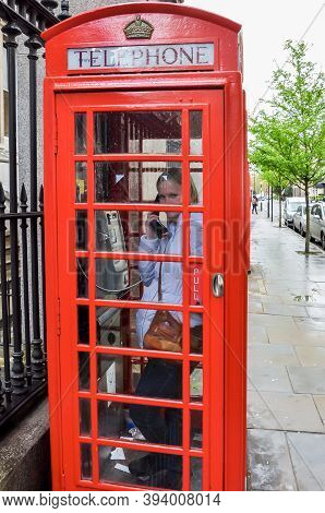Young Woman Making A Call In Red Telephone Box, London, Uk - April 2018