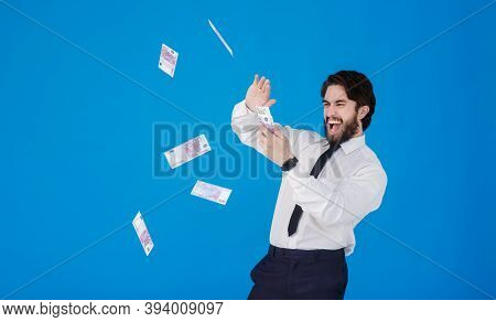 A Young Cheerful Bearded Businessman In A White Shirt And Black Tie On A Blue Background Splashes Mo