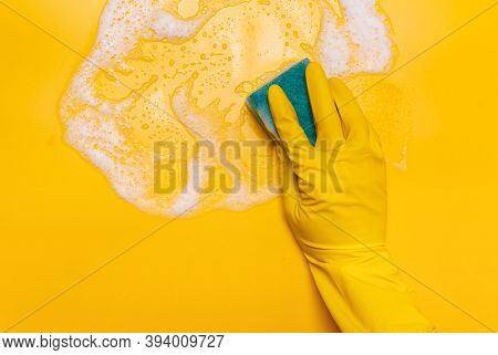 Wipe The Foam On A Yellow Background With A Blue Gloved Sponge.