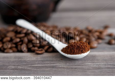 White Ceramic Spoon With Ground Coffee On A Wooden Background Fried Arabica Grains.