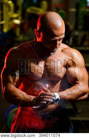 Sporty Handsome Strong Man Posing On The Background Of The Gym. A Strong Bodybuilder With Perfect Ab