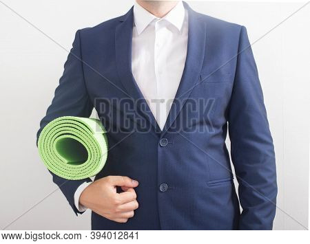 A Young Business Man In A Suit And Jacket Stands And Holds A Exercise And Yoga Mat Close At Hand. Th