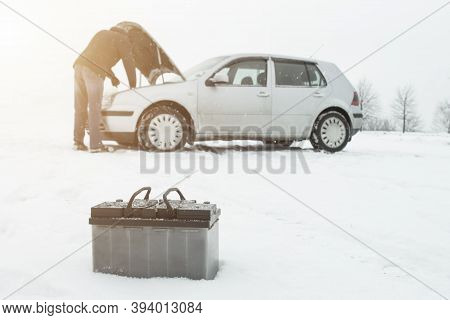 A Man Repairs A Car In Winter On Snow In The Background Is A Discharged Battery, Copy Space