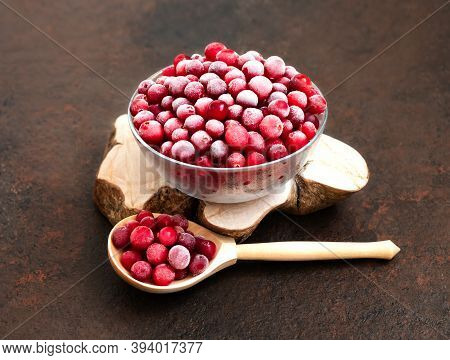 Frozen Cranberries In A Bowl And Wooden Spoon On A Brown Background. Frozen Healthy Food. Side View.