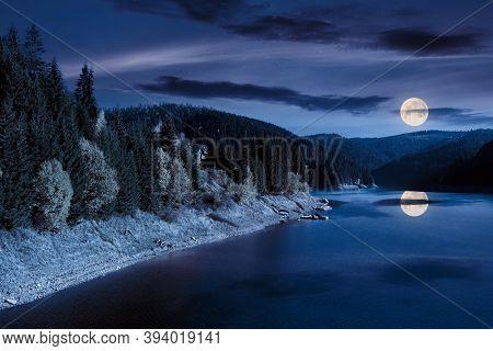 Mountain Lake In Autumn Season At Night. Beautiful Countryside Scenery In Full Moon Light. Blue Sky