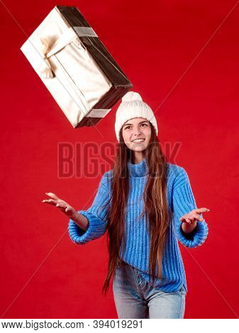 A Girl In A Blue Sweater And A White Hat Catches Gifts In The Air On A Red Background.
