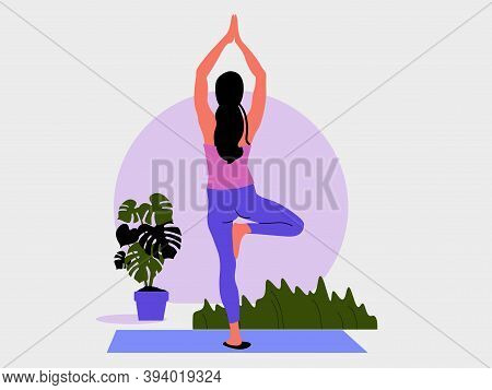 Young Woman Stands In A Yoga Pose Tree And Meditates. The Girl Doing The Stretching Exercises At Hom