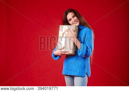 Girl In A Blue Sweater Holding A Gift In Her Hands On A Red Background.