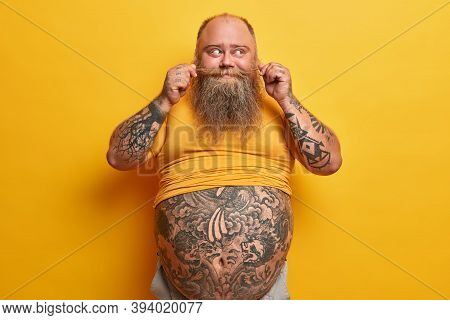 Studio Portrait Of Bearded Man Has Overweight, Has Big Stomach And Fat Belly, Curls Mustache And Thi