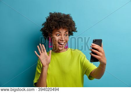 Happy Curly Haired Millennial Girl Takes Selfie On Smartphone, Has Conversation On Video Call And Wa
