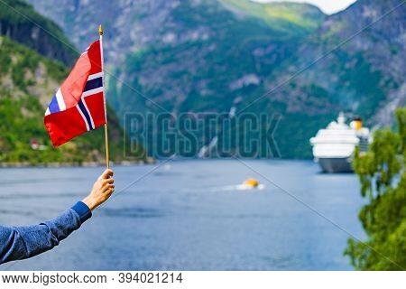Female Tourist With Norwegian Flag Enjoying Fjord Geirangerfjord View With Cruise Ship. Cruising Vac