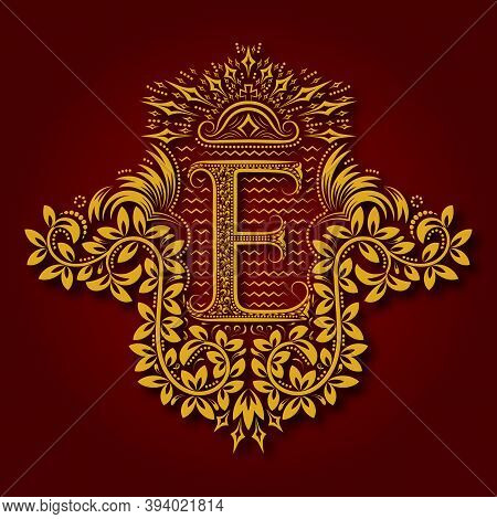 Letter E Heraldic Monogram In Coats Of Arms Form. Vintage Golden Logo With Shadow On Maroon Backgrou