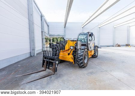 Industrial warehouse construction. Rotating telehandler vehicle. Building a new hall or storehouse.